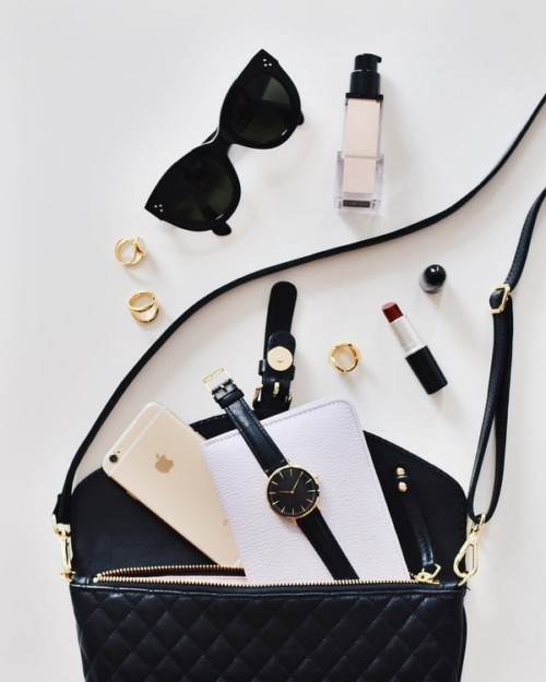 Black handbag on white table, assorted items lay in front of it, sunglasses, lipstick, rings, a watch, and makeup.