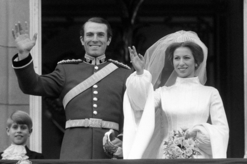 Princess Anne and her husband at her first wedding waving at the crowd. She is in bridal white with the Queen Mary Fringe Tiara.