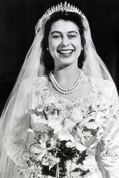 Queen Elizabeth II in her wedding gown with a bouquet of flowers a double strand of pearls and the Queen Mary Fringe Tiara with a bridal veil.