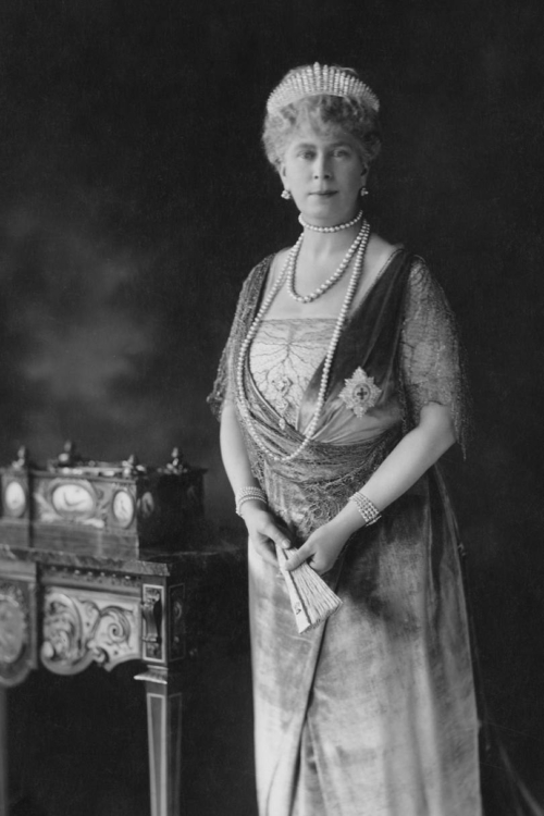 greyscale image of Queen Mary of England standing regally decked out in a fine gown, jewels, and The Queen Mary Fringe Tiara