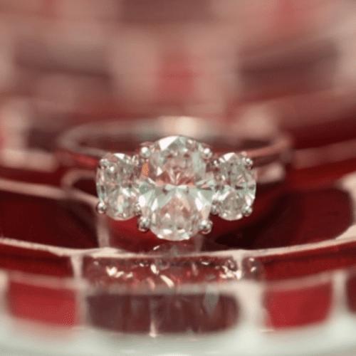 three-stone oval diamond ring set on glass that looks like red bricks