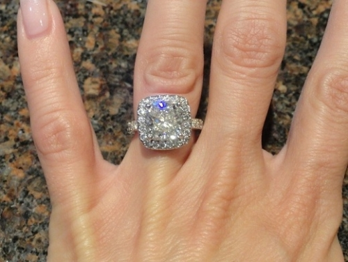4 fingers held over a countertop with a stunning cushion modified brilliant diamond ring.