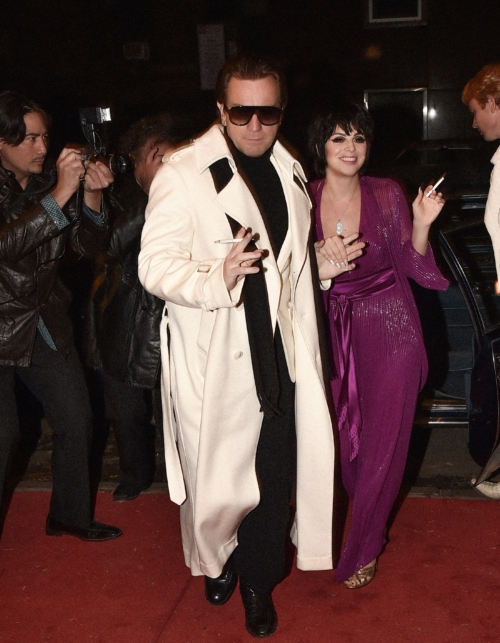 a man in a white duster over a black suit leading a brunette woman in a purple dress on a red carpet with paparazzi
