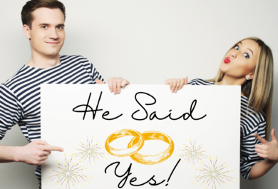 """brunette man and blonde woman, both in white and black striped shirts holding a banner that says """"He said yes"""" in a handwriting font, with golden fireworks and 2 gold rings illustrated on the banner."""