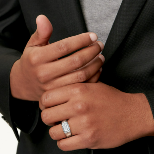 brown men's hands in front of a suited chest with a stunning men's ring on the ring finger with a large diamond.