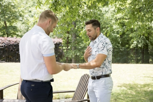 Taller blonde man in a white shirt and black pants proposing to a shorter bearded brunette man in a printed top and white pants. They are outdoors in front of an Adirondack chair.