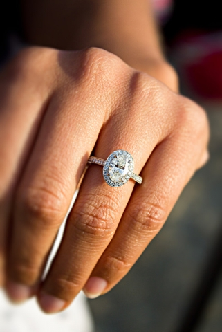 oval diamond ring in halo on beautiful long fingers