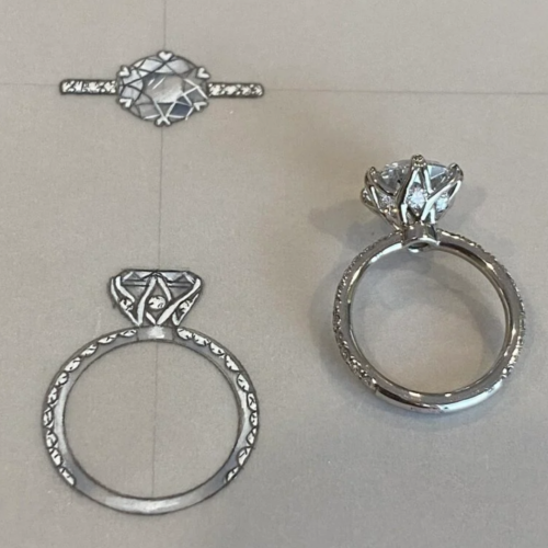 A diamond ring on paper along with the drawings that inspired it