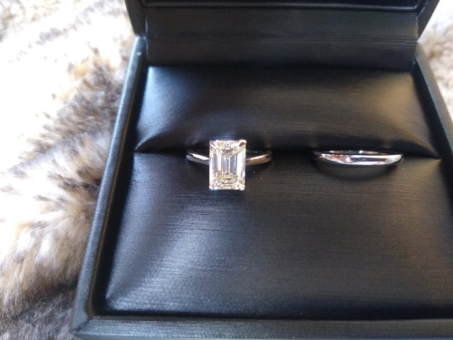 Black ring box with a silver wedding band and an emerald cut diamond ring.