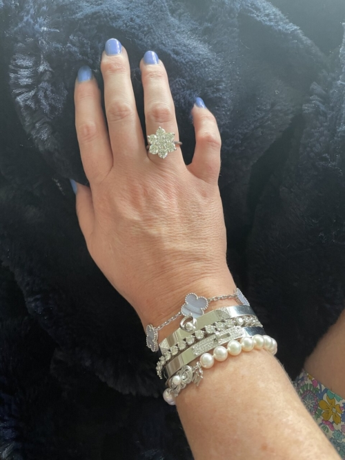 A feminine hand and wrist with stacks of fabulous bracelets and a gorgeous diamond cluster ring on the ring finger.