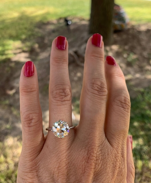 Large disco ball style diamond ring on a feminine hand with red painted nails. green grass in the background.
