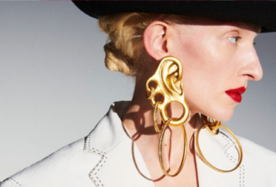 a blond woman in a black hat looks to the side, she is wearing a white shirt and has a bright red lip/ Her giant exaggerated earrings include what looks like a hybrid between a golden ear and brass knuckles with giant hoops hanging from them.