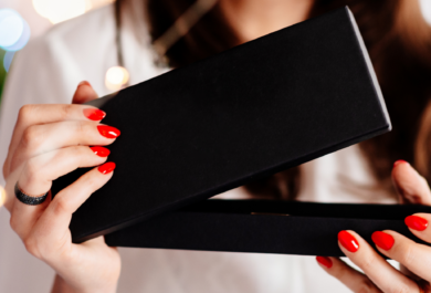 feminine hands opening a black gift box.